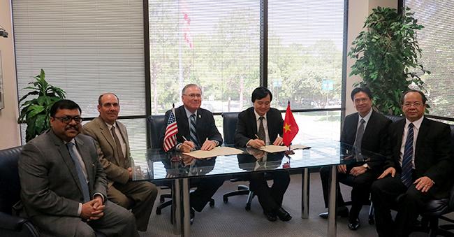 Giám đốc ĐHQGHN Phùng Xuân Nhạ và Giám đốc UHCL William A. Staples đại diện cho 2 ĐH kí kết văn bản hợp tác song phương.